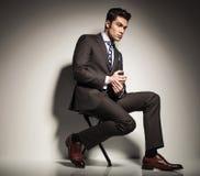 Укомплектуйте личным составом сидеть с одной ногой перед другим Стоковая Фотография