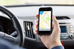 Укомплектуйте личным составом сидя автомобиль держа телефон с nav интерфейса Стоковое Фото