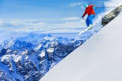 Укомплектуйте личным составом скакать от утеса, катаясь на лыжах на свежем снеге порошка Стоковое Фото