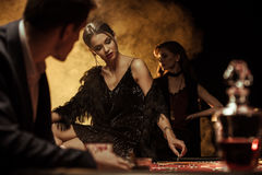 Укомплектуйте личным составом смотреть женщину сидя на таблице покера в казино стоковые фотографии rf