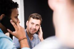 Укомплектуйте личным составом смотреть коллеги говоря на smartphone на малой встрече офиса Стоковые Фотографии RF