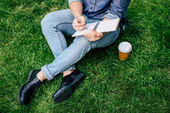 Укомплектуйте личным составом сочинительство на тетради и выпивая кофе от бумажного стаканчика пока сидящ на зеленой траве Стоковая Фотография