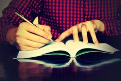 Укомплектуйте личным составом сочинительство руки на тетради на столе в доме Стоковая Фотография RF