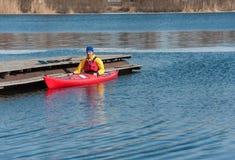 Укомплектуйте личным составом сплавляться на красном каяке на реке 01 Стоковое Фото