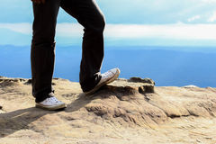 Укомплектуйте личным составом стойку на утесе горного пика и покройте горный вид Стоковая Фотография