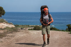 Укомплектуйте личным составом с большим рюкзаком a на море дороги Стоковые Фото