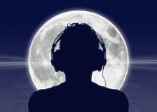 Укомплектуйте личным составом слушать к музыке на полнолунии Стоковое фото RF