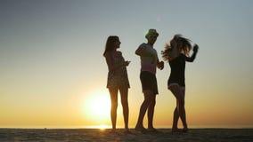 Укомплектуйте личным составом танцы с 2 женщинами на пляже на заходе солнца сток-видео