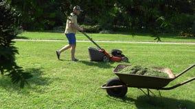 Укомплектуйте личным составом траву вырезывания парня в его дворе сада с травокосилкой около пути 4K видеоматериал