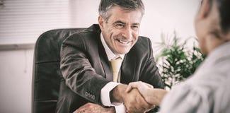 Укомплектуйте личным составом трясти руку женщины в офисе Стоковое Изображение RF