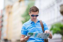 Укомплектуйте личным составом туриста с картой города и рюкзака в улице Европы Кавказский мальчик смотря с картой европейского го стоковое изображение rf