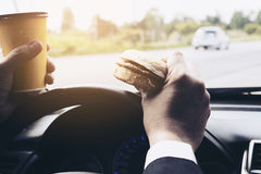 Укомплектуйте личным составом управлять автомобилем пока держащ чашку холодного кофе и ел гамбургер Стоковая Фотография RF