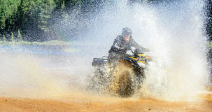 Укомплектуйте личным составом управлять квадом ATV до брызгать воду с быстрым ходом Стоковое фото RF