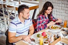 Укомплектуйте личным составом усмехаться на обеде пока сидящ около девушки Стоковое фото RF