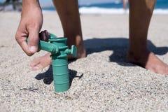 Укомплектуйте личным составом устанавливать хватальщик зонтика пляжа Стоковые Фото