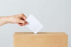 Укомплектуйте личным составом установку его голосования в урну для избирательных бюллетеней на избрание стоковое фото rf