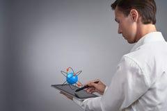 Укомплектуйте личным составом ученого держа ПК таблетки с моделью атома, концепцией исследования Стоковое фото RF