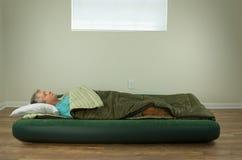 Укомплектуйте личным составом удобно спать на кровати тюфяка воздуха крупного плана в спать стоковое фото