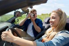 Укомплектуйте личным составом фотографировать женщину управляя автомобилем камерой фильма Стоковая Фотография RF