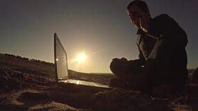 Укомплектуйте личным составом фрилансера бизнесмена говоря на телефоне работая за компьтер-книжкой сидя на пляже работать силуэт  Стоковая Фотография RF