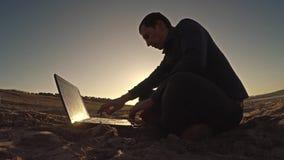 Укомплектуйте личным составом фрилансера бизнесмена компьтер-книжки работая за сидеть на пляже работать силуэт в солнце сток-видео