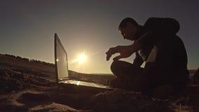Укомплектуйте личным составом фрилансера бизнесмена работая за компьтер-книжкой сидя на пляже работать силуэт в солнце Стоковое Фото