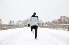 Укомплектуйте личным составом ход вдоль покрытой снегом дороги моста зимы Стоковое фото RF