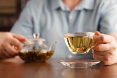 Укомплектуйте личным составом чашку владением в руке и предложите чай стоковое изображение rf