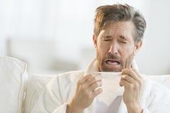 Укомплектуйте личным составом чихать в ткань Стоковая Фотография RF