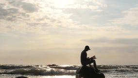 Укомплектуйте личным составом чтение на утесе в бурном море против съемки тележки солнца видеоматериал