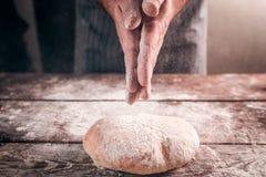 Укомплектуйте личным составом шлепок его руки над крупным планом свежего хлеба Стоковые Изображения RF