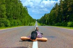 Укомплектуйте личным составом hiker лежа на переходе дороги ждать Стоковые Изображения