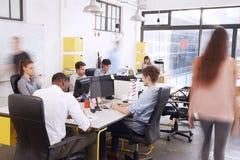 Укомплектуйте штаты идти через занятый открытый офис плана Стоковые Изображения