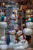 Украина, Львов - 6-ое декабря 2018 Счастливые снеговики в красочных шляпах, с шарфами магазин витрины стоковая фотография