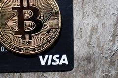 Украина, Kremenchug - март 2019: Золотое Bitcoin на кредитной карточке visa стоковые изображения