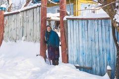 Украина, Svirzh, St Lesnaya - 13-ое января 2019: Старая бабушка стоит около ее дома в деревне в зиме стоковые фотографии rf
