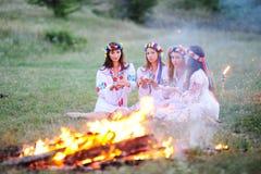 Украинская девушка в рубашках сидя вокруг лагерного костера Стоковая Фотография