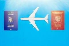 Украинские и русские паспорта и модели самолета Концепция возобновления воздушного движения между странами стоковая фотография