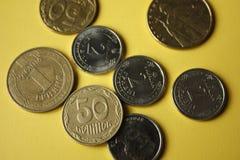 Украинские монетки изолированные на желтой предпосылке Монетки конца-вверх расположены в центре рамки деньги дома владельцев дома стоковая фотография