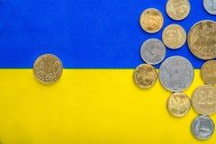 Украинские национальные монетки и 10 центов евро на фоне национального желт-голубого флага Валюта Евровидения Стоковое Фото