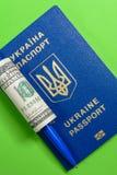 Украинский биометрический пасспорт с 100 долларовыми банкнотами и ручкой Стоковые Изображения