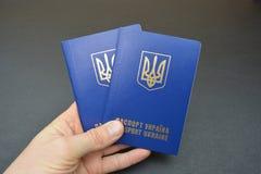 Украинский пасспорт в руке на черной предпосылке Стоковая Фотография RF
