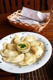 Украинское и русское vareniki блюда с картофельными пюре и соусом сметаны и гриба на белой плите конец вверх Стоковое фото RF