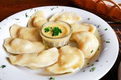 Украинское и русское vareniki блюда с картофельными пюре и соусом сметаны и гриба на белой плите конец вверх Стоковое Фото