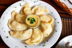 Украинское и русское vareniki блюда с картофельными пюре и соусом сметаны и гриба на белой плите конец вверх Стоковые Фото