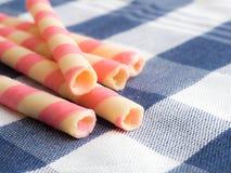 Украсьте дырочками striped крены вафли на голубой скатерти шотландки Стоковая Фотография RF