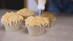 Украшать булочки с оранжевой сливк Хлебопек кладя сливк масла на вкусные торты акции видеоматериалы