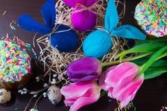Украшать пасхи Пасхальные яйца в форме кролика в гнезде с ветвью вербы, тюльпанами и тортами пасхи стоковое фото