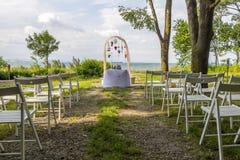 Украшение белых стульев, дуга свадьбы цветков ожидает своего жениха стоковое фото