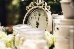 Украшение в белых цветах от старых часов, свечей, цветков стоковые изображения